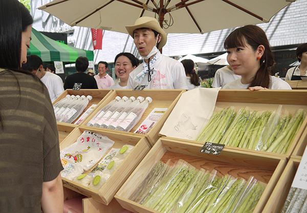 ▲ボランティアスタッフが商品知識を学び、北海道フードフロンティア バイヤーの久富恵里花さん(ブース奥)が販売指導を行いました
